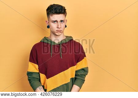 Young caucasian boy with ears dilation wearing casual sweatshirt skeptic and nervous, frowning upset because of problem. negative person.