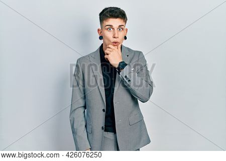 Young caucasian boy with ears dilation wearing business jacket looking fascinated with disbelief, surprise and amazed expression with hands on chin