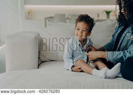 Young Caring Mother Dressing Up Her Little Cute Son With Curly Hair, Putting On Adorable Boy Shirt A