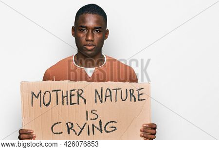 Young african american man holding mother nature is crying protest cardboard banner thinking attitude and sober expression looking self confident