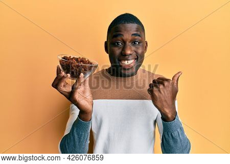 Young african american man holding bowl with raisins pointing thumb up to the side smiling happy with open mouth