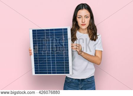 Young beautiful girl holding photovoltaic solar panel thinking attitude and sober expression looking self confident