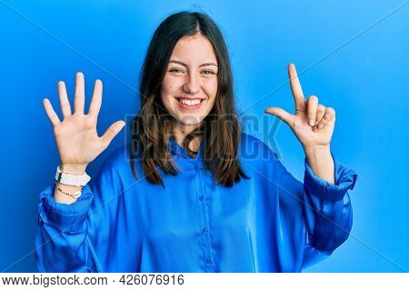 Young brunette woman wearing casual blue shirt showing and pointing up with fingers number seven while smiling confident and happy.