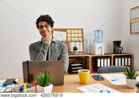 Young hispanic man wearing business style sitting on desk at office looking confident at the camera smiling with crossed arms and hand raised on chin. thinking positive.