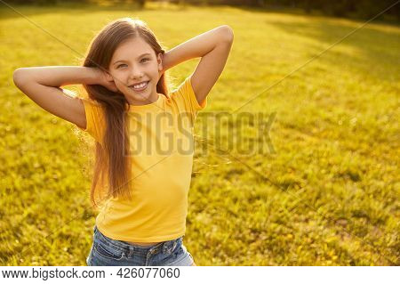 Happy Preteen Girl In Yellow T Shirt Smiling And Looking At Camera While Standing On Blurred Green M
