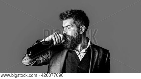 The Person Holds A Red Wine Bottle In A Hand. Bearded Man With A Bottle Champagne Of And Glass. Styl
