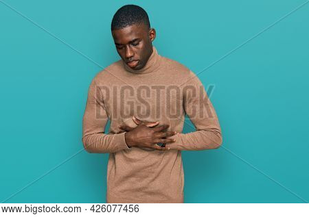 Young african american man wearing casual winter sweater with hand on stomach because indigestion, painful illness feeling unwell. ache concept.