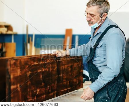 A Gray-haired Carpenter With Glasses Works With Wood On A Workbench In A Carpentry Shop. A Pensioner