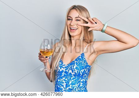Young beautiful caucasian woman drinking a glass of white wine doing peace symbol with fingers over face, smiling cheerful showing victory