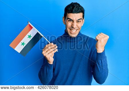 Handsome hispanic man holding syria flag screaming proud, celebrating victory and success very excited with raised arm