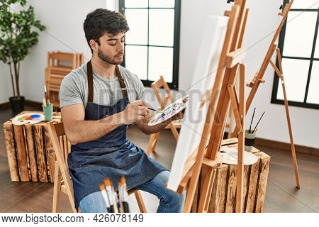Young hispanic artist man concentrated painting at art studio