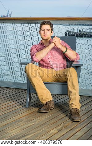 Dressing In A Light Red Shirt, Dark Yellow Pants And Brown Shoes, A Young Handsome Guy Is Sitting On
