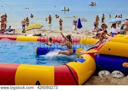 Zaliznyi Port, Ukraine - July 23, 2020: Children Have Fun On An Inflatable Rubber Water Slide On The