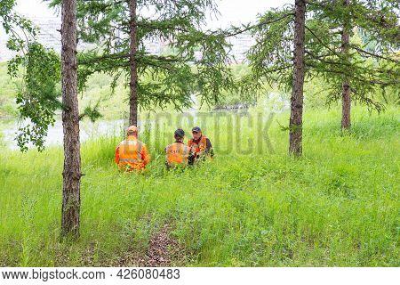 Krasnoyarsk, Russia - June 28, 2021: Workers In Orange Service Suits Rests On Lawn. A City Utility W