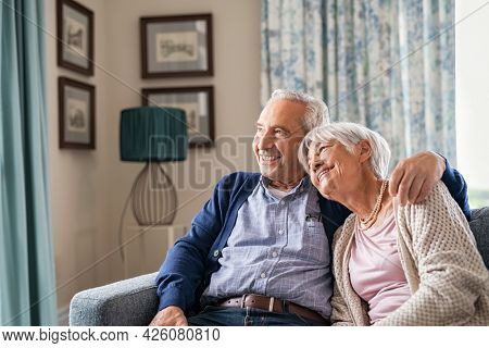 Romantic senior couple smiling and looking away at home. Happy smiling old man hugging wife while sitting on sofa. Retired couple in love relaxing at home while planning their next holiday.