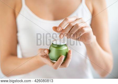 Closeup shot of hands applying moisturizer. Beauty woman holding a green glass jar of skin cream. Beautiful girl holding biological moisturizer jar.