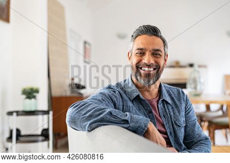 Portrait of handsome mature man relaxing on couch at home while looking at camera. Mixed race man in casual clothing sitting on sofa and smiling with copy space. Successful happy middle eastern guy.