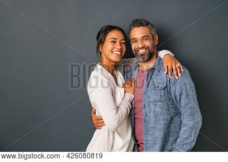 Portrait of happy mid adult couple embracing and looking at camera standing against gray background. Mature indian man in love standing on grey wall while hugging his hispanic woman with copy space.