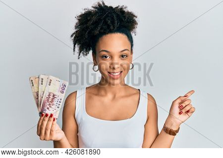 Young african american girl holding 500 new taiwan dollars banknotes smiling happy pointing with hand and finger to the side