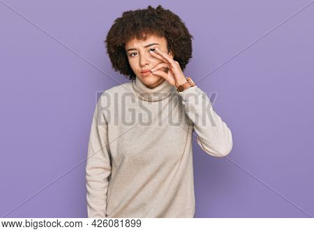 Young hispanic girl wearing wool winter sweater mouth and lips shut as zip with fingers. secret and silent, taboo talking
