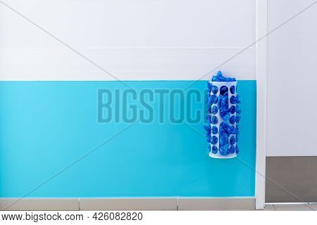 A Dispenser With Shoes On The Wall At The Medical Facility. Blue And White Wall Paint, Copyspacel