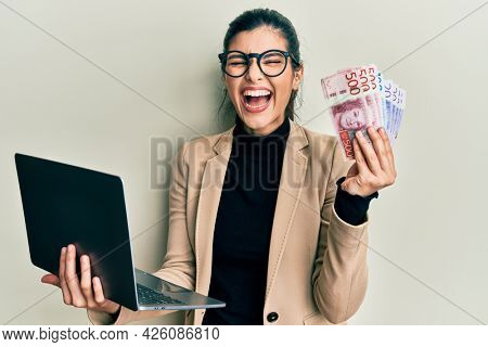Young hispanic woman wearing business style holding laptop and swedish krone smiling and laughing hard out loud because funny crazy joke.