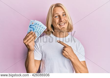 Caucasian young man with long hair holding 50 thai baht banknotes smiling happy pointing with hand and finger