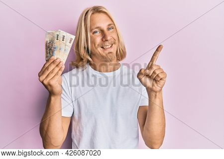 Caucasian young man with long hair holding 500 new taiwan dollars banknotes smiling happy pointing with hand and finger to the side