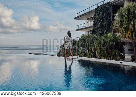 Backview Shot Of Woman Walking Around Swimming Pool