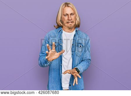 Caucasian man with blond long hair wearing casual denim jacket disgusted expression, displeased and fearful doing disgust face because aversion reaction.