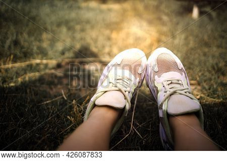 Closeup Of Feet In White Sneakers On Grass. Relaxation And Outdoor Idea Concept.