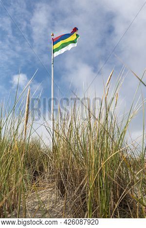 Characteristic Striped Flag Of The Wadden Island Of Terschelling On A Dune Against A Blue Sky With W