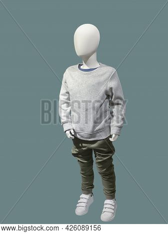 Full Length Image Of A Child Display Mannequin Dressed In Gray Sweater And Khaki Trousers Isolated O