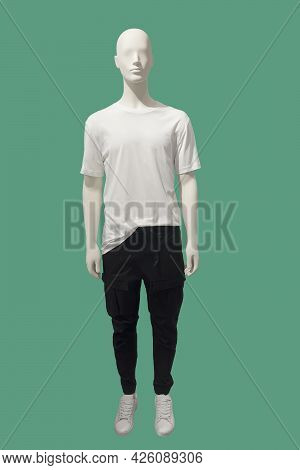 Full Length Image Of A Male Display Mannequin Wearing White T-shirt And Black Trousers Isolated On A