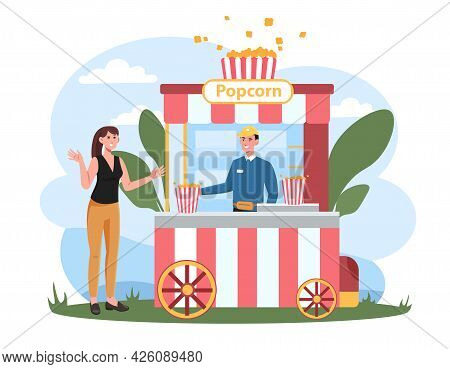 Concept Of Selling Popcorn. Seller Stands Behind A Mobile Counter And Offers The Girl Popcorn. A Del