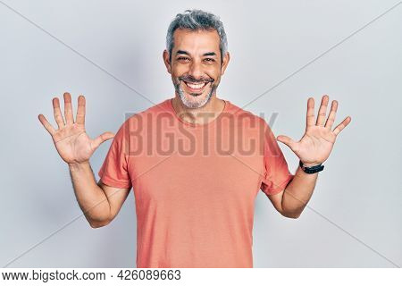 Handsome middle age man with grey hair wearing casual t shirt showing and pointing up with fingers number ten while smiling confident and happy.