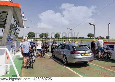 Cuijk, The Netherlands - June 18, 2021: Small Ferry With Cars, Bicycles And Pedestrians Over River M