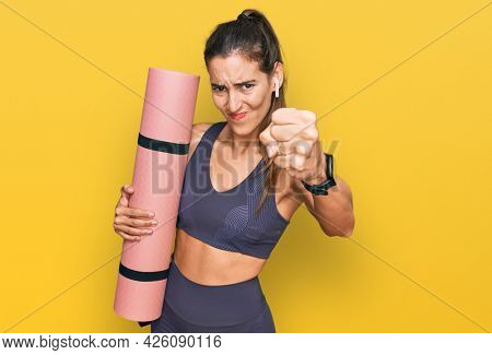 Young beautiful woman wearing sportswear holding yoga mat annoyed and frustrated shouting with anger, yelling crazy with anger and hand raised