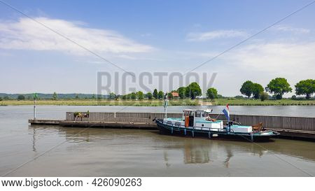 River Meuse With Moored Tugboat In Harbor Dutch Village Cuijk