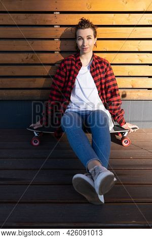 Relaxed Stylish Girl Skateboarder Having Rest After Longboarding Sit On Longboard Skate Smiling. Tre