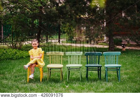 A Laughing, Cheerful Girl In A Yellow Dress Sits On Viennese Multicolored Painted Chairs Waiting For