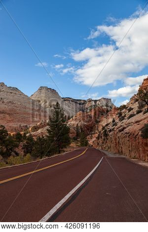 A Red Asphalt Road Leading Into The Spectacular Landscape Of Zion National Park With Eroded Rock Mou