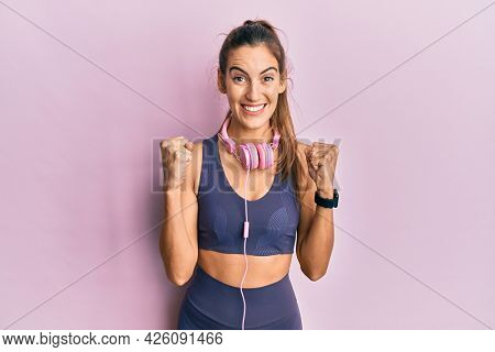 Young beautiful woman wearing gym clothes and using headphones celebrating surprised and amazed for success with arms raised and open eyes. winner concept.