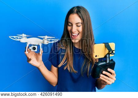 Young beautiful woman taking a selfie photo with smartphone flying drone smiling and laughing hard out loud because funny crazy joke.
