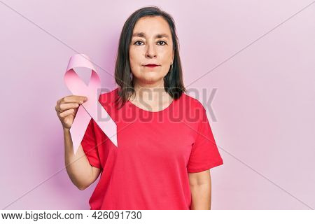 Middle age hispanic woman holding pink cancer ribbon thinking attitude and sober expression looking self confident