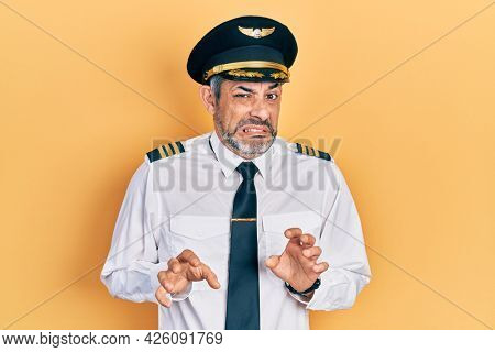 Handsome middle age man with grey hair wearing airplane pilot uniform disgusted expression, displeased and fearful doing disgust face because aversion reaction.