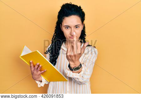 Young hispanic woman with curly hair holding book showing middle finger, impolite and rude fuck off expression