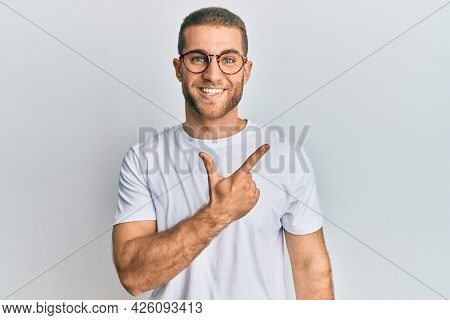 Young caucasian man wearing casual clothes and glasses cheerful with a smile of face pointing with hand and finger up to the side with happy and natural expression on face