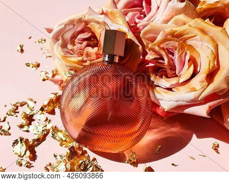 Unbranded Brown Perfume Bottle With Trend Shadow, Pink Gold Roses And Pieces Of Golden Paper On Pink