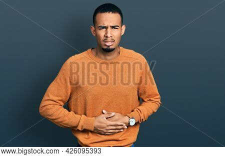 Young african american man wearing casual clothes with hand on stomach because indigestion, painful illness feeling unwell. ache concept.